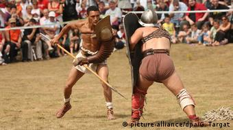 Two men in gladiator clothing fight with spears and shields (picture-alliance/dpa/G. Targat)