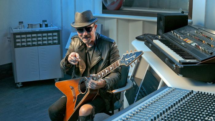 Rock musician Rudolf Schenker sits in a recording studio in front of a piano. He is wearing sunglasses, a hat and leather jacket and holding a uniquely shaped guitar
