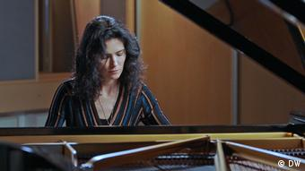 Pianist Katie Mahan plays a grand piano in a striped dress. We see her from the torso up as she looks down at the keys, playing intently.