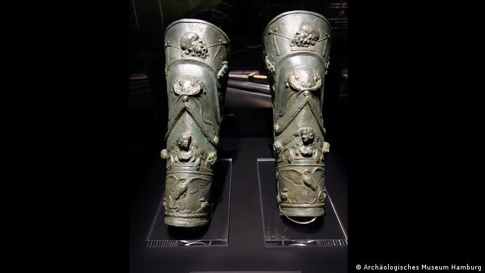 Two metal leg guards are richly decorated with figures and animals.  (Archäologisches Museum Hamburg)