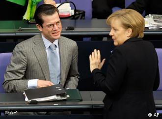 Merkel shares a glance with defense minister Karl-Theodor zu Guttenberg in the Bundestag
