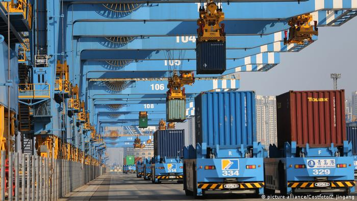 Containers at the Port of Qingdao in Qingdao City are lifted by cranes from unmanned trucks to be loaded onto a ship on a quay on January 1st, 2020