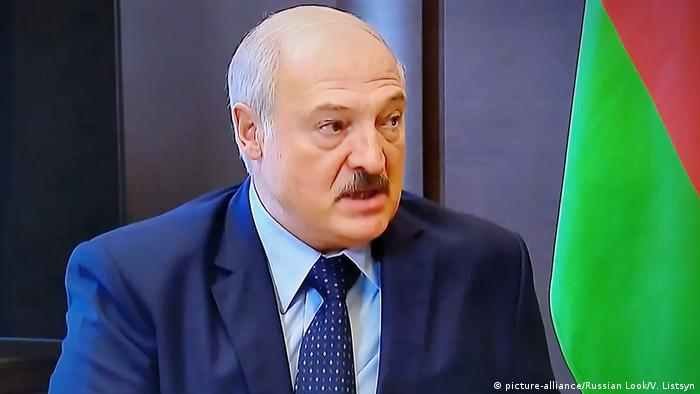 A close up of Lukashenko's face next to a Belarus flag. He has a small mustache and is wearing a blue jacket, light blue shirt and a spotted blue tie.