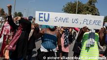 Asylum-seekers on Lesbos at a protest hold a sign that reads EU save us, please (picture-alliance/dpa/P. Giannakouris)