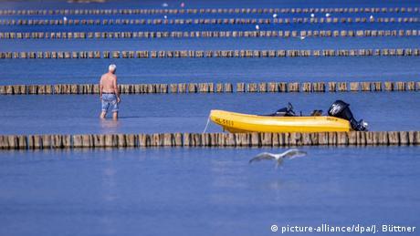 Čovek u plitkoj vodi između redova niskih brana. Turisti u Redevišu u Meklenburgu Prednjoj Pomeraniji koriste poslednje dane leta i temperature iznad 26 stepeni da posete još jednom Baltičko more.