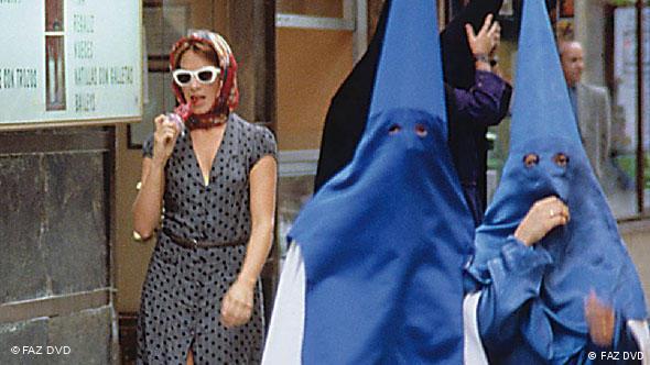 Frau neben mit Kaputzen verhüllten Männern eines Umzugs - Szene aus Bin ich schön? (Foto: FAZ DVD)