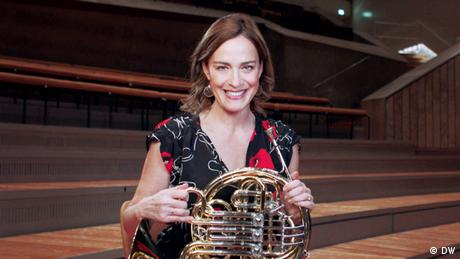 Sarah Willis holds a french horn, smiling. She is sitting in a rehearsal hall.