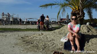 Germany Munich | A woman sitting on the sand under a palm tree
