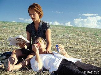 Junge Frau hält auf einem Feld jungen liegenden Mann in den Armen - Szene aus Bin ich schön? (Foto: FAZ DVD)