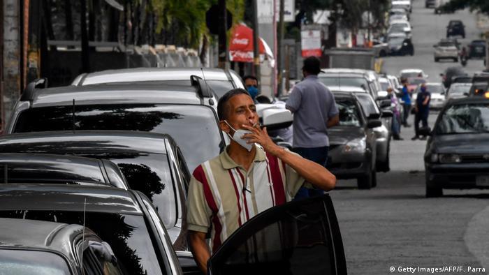 Menschen warten vor ihren Autos in Caracas vor einer Tankstelle