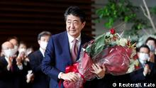 Japan's outgoing Prime Minister Shinzo Abe holds a bouquet of flowers presented by staff members of the official prime minister's residence, as he leaves the premises, in Tokyo, Japan September 16, 2020. REUTERS/Issei Kato