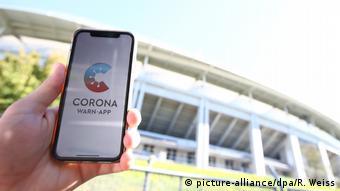Человек держит в руке смартфон, на экране которого открыто мобильное приложение Corona-Warn-App