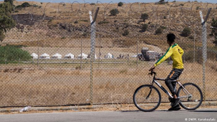 A refugee man on a bicycle stops to look at the newly built temporary camp that was set up on Lesbos after Moria's destruction. (DW/M. Karakoulaki)