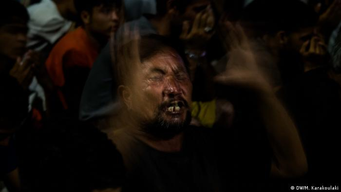An Afghan man who fled the Moria fire breaks into tears when he sees DW filming him while praying, stops his prayer and starts talking about his children while crying nonstop (DW/M. Karakoulaki)