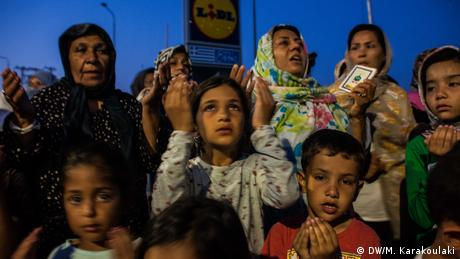 A young girl takes part in a prayer with men, women and children and prays for the conditions to become better for those sleeping rough after the fire at Moria camp on the island of Lesbos (DW/M. Karakoulaki)