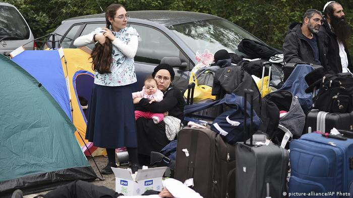 A Hasidic Jewish woman is dressed in black. She is holding a small baby on her knees and is crouched between suitcases and tents. Another woman stands in the foreground, wearing a long skirt and tying her hair.