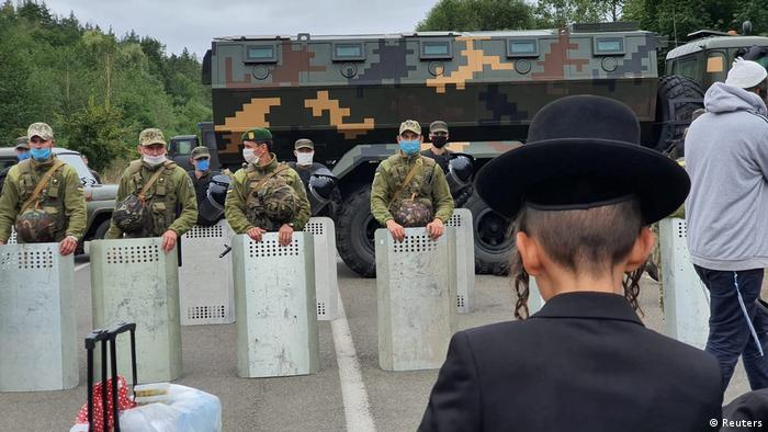 A Hasidic jew stands in front of border guards holding riot shields