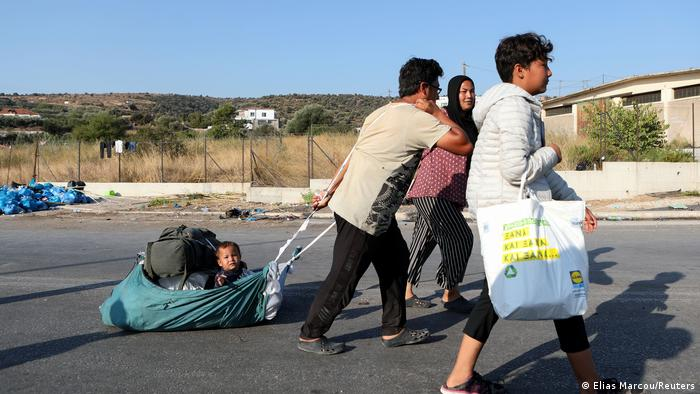 A man pulls a baby as refugees and migrants from the destroyed Moria move towards a new temporary camp