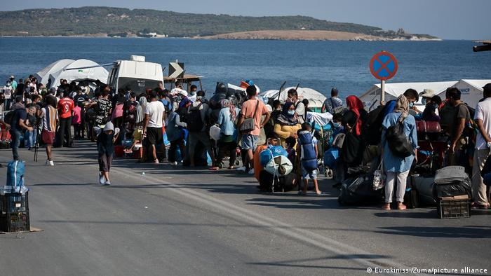 Migrants carry their belongings as they flee a road leading from Moria to the capital of Mytilene, on the northeastern island of Lesbos
