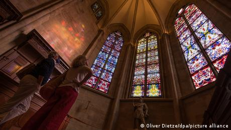 Two persons looking at Gerhard Richter's windows at Tholey Abbey (Oliver Dietze/dpa/picture alliance)