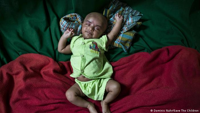 A sleeping baby with arms stretched out, on red and green blankets (Dominic Nahr/Save The Children)