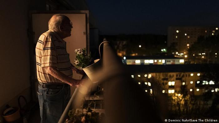 Ein Senior steht auf einem Balkon und blickt auf Lichter einer Stadt. Foto aus dem Bildband Ich lebe mit Bildern von Dominic Nahr für Save the Children. (Dominic Nahr/Save The Children)