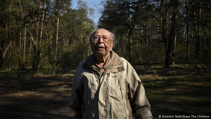 A senior man walking the forest looks up at the sky (Dominic Nahr/Save The Children)