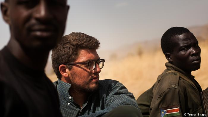 Der Fotograf Dominic Nahr steht zwischen zwei Menschen aus dem Südsudan. (Trevor Snapp)