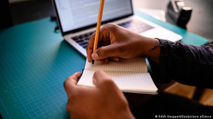 Estudante escreve em caderno diante de computador