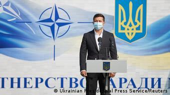 Владимир Зеленский на фоне эмблемы НАТО и герба Украины