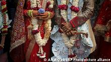 A newly wed Indian couple poses for photographs during a mass marriage ceremony for eight couples in New Delhi, India, Friday, March 8, 2019. Mass weddings in India are organized by social organizations primarily to help economically backward families who cannot afford the high ceremony costs as well as the customary dowry and expensive gifts that are still prevalent in many communities. (AP Photo/Altaf Qadri) |