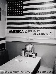 In einem amerikanischen Diner hängt ein Plakat mit der US-Flagge und der Aufschrift: America - Love it... or leave it! (Courtesy The Jerry Berndt Estate 2020)