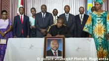 FILE - In this Saturday, June 13, 2020 file photo, Burundi's president-elect Evariste Ndayishimiye, center, accompanied by his wife Angeline Ndayubaha, right, signs the book of condolences, above a photograph of the late President Pierre Nkurunziza, at the presidential palace in Bujumbura, Burundi. A new report released Thursday, Sept. 17, 2020 by the United Nations commission of inquiry on Burundi sees little optimism in the government of new President Evariste Ndayishimiye, saying it is extremely concerned that he has appointed senior officials who face international sanctions for alleged human rights abuses in the country's 2015 political turmoil. (AP Photo/Berthier Mugiraneza, File) |