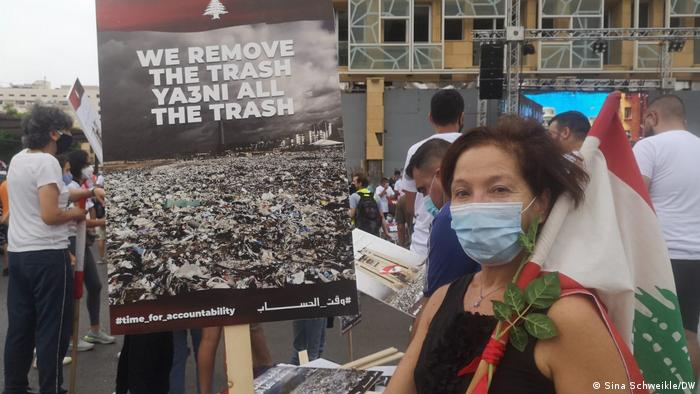 Laila Zahed with Lebanese flag, board saying 'we remove all the trash'