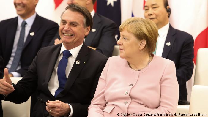 O presidente brasileiro, Jair Bolsonaro, e a chanceler federal da Alemanha, Angela Merkel, sentados um ao lado do outro durante uma cúpula do G20 no Japão em 2019