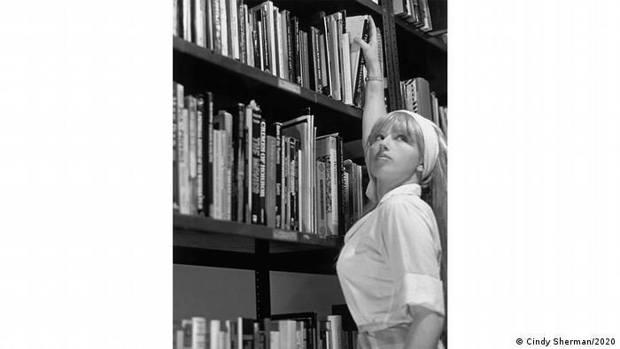 Schwarzweiß-Foto von Cindy Shermanzeigt eine Frau vor einem Bücherregal in weißer Bluse und Kopftuch. Zu sehen in der Fondation Louis Vuitton (Cindy Sherman/2020)