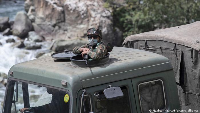 An Indian army soldier keeps guard on top of his vehicle