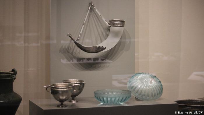 Vitrine de museu com vasos romanos e tigelas de vidro e um típico chifre germânico para bebidas