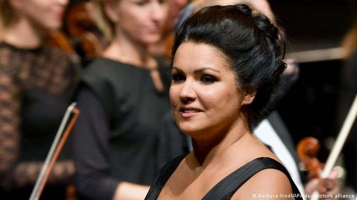 Opera singer Anna Netrebko in a black dress performing in front of an orchestra