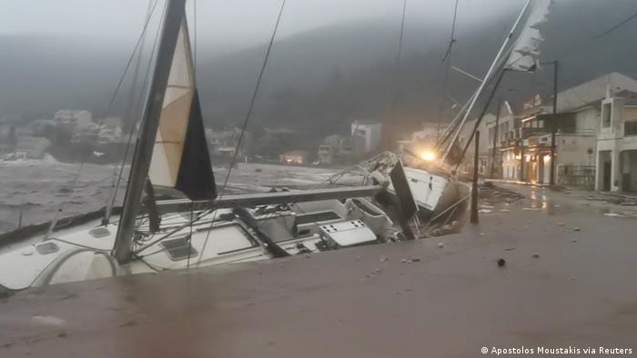 A boat is battered against a harbor wallk during storm Ianos