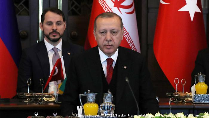 Berat Albayrak (belakang) mendampingi Presiden Turki, Recep Tayyip Erdogan, saat menjamu Presiden Iran, Hassan Rouhani, dan Presiden Rusia, Vladimir Putin, di Istana Kepresiden di Ankara, April 2018.