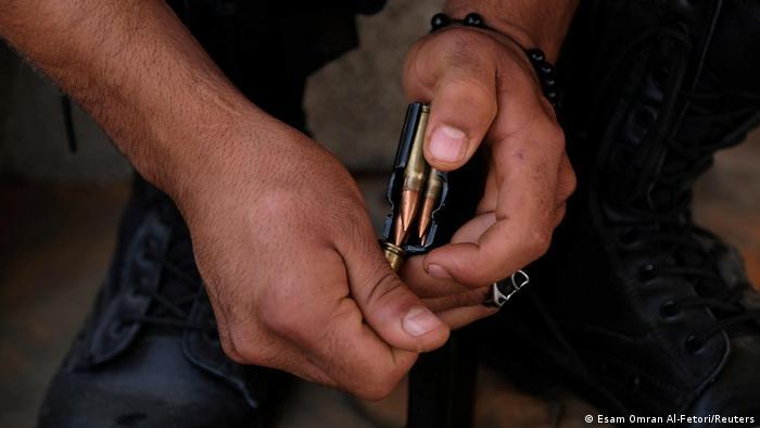 Foto simbólica de unas manos que cargan balas de un fusil.