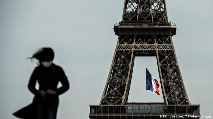 A woman wears a mask in front of the Eiffel Tower (Philippe Lopez/AFP/Getty Images)