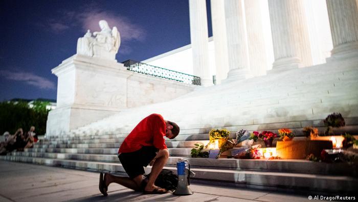 A man kneels before a makeshift memorial on the Supreme Court steps (Al Drago/Reuters)
