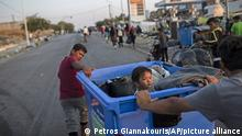 A child sits inside a recycle bin as a boy and man pull their belongings on the northeastern island of Lesbos, Greece, Friday, Sept. 18, 2020. Police on the Greek island of Lesbos resumed an operation Friday to move migrants made homeless by fires to new camp amid a local COVID-19 outbreak. It came a day after 5,000 people were taken to the army-built camp, 135 testing positive for the new coronavirus. (AP Photo/Petros Giannakouris) |