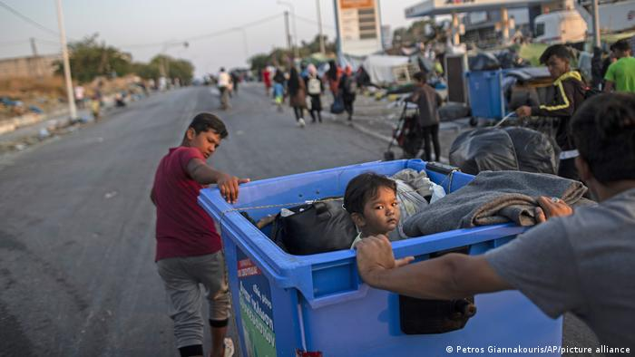A man and a boy moving a recycling bin with their belongings and a child inside (Petros Giannakouris/AP/picture alliance)