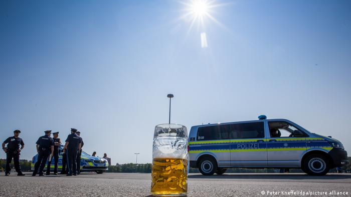 A half empty glass of beer on the floor in front of police officers (Peter Kneffel/dpa/picture alliance)