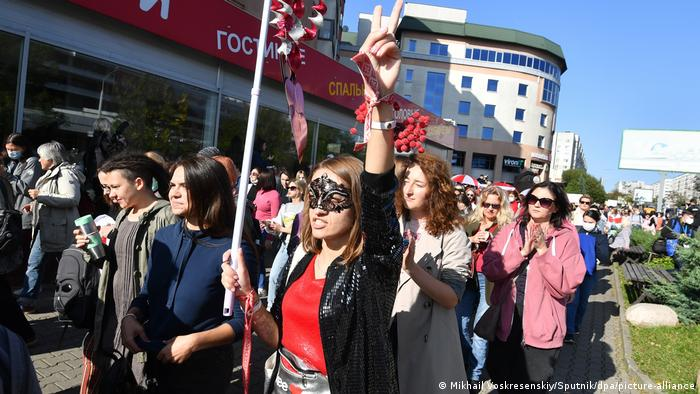 a woman wears a black glittery eye mask and holds a red and white windmill on the end of a stick with one arm raised. She is shouting. She is in a crowd of protesters.