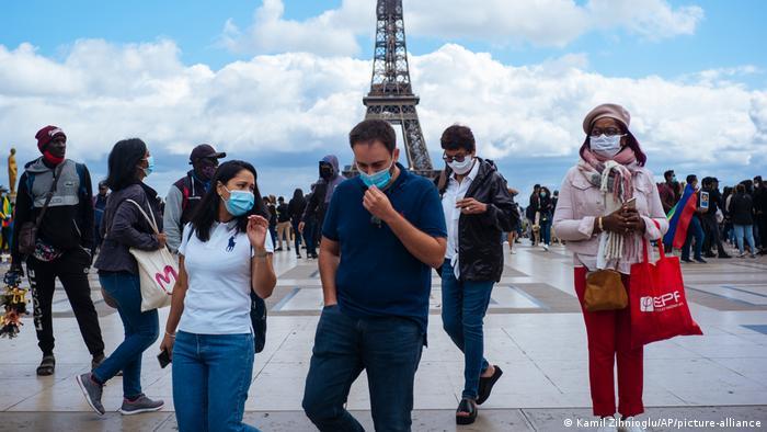 People wear face masks near the Eifel tower