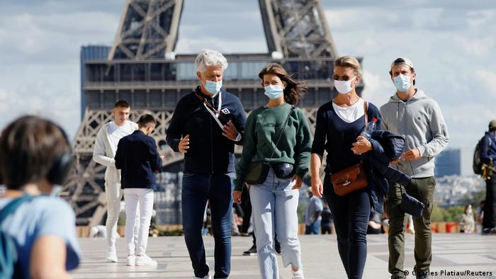 People walk with protective masks near the Eiffel Tower in Paris, France. Reuters/Charles Platiau